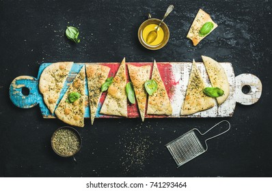 Homemade Italian focaccia flatbread cut into pieces with herbs, fresh basil leaves, olive oil and glass of rose wine on colorful painted wooden board over black stone background, top view