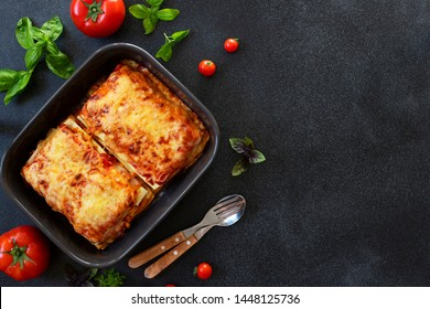 Homemade Italian Lasagna with Tomato Sauce and Chicken, Served with Tomatoes and Basil. Two portions. Dark background. Top view. Copy space