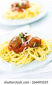 Homemade Italian meatballs garnished with cilantro and parmesan cheese over spaghetti for dinner.