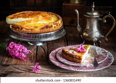 Homemade Italian ricotta cheesecake and pink hyacinths on wooden background. Rustic style dark photography.