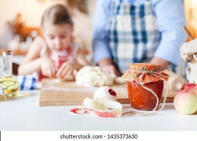 Homemade jam, apples, cute orange jar, dough and fall harvest foods are on table. Family is cooking pie in cozy home kitchen. Grandmother and child prepare autumn pastries for Thanksgiving dinner