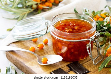 Homemade jam. Glass jar with sea buckthorn jam on rustic background. Preserved berry. Copy space.