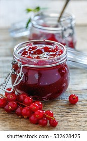 Homemade jam of red currants in a glass jar on old wooden table.