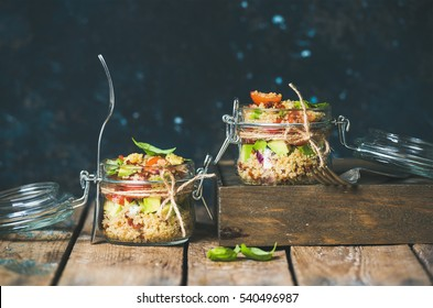 Homemade jar quinoa salad with cherry and sun-dried tomatoes, avocado and fresh basil. Detox, dieting, vegetarian, vegan, clean eating food concept. Dark blue background, selective focus, copy space
