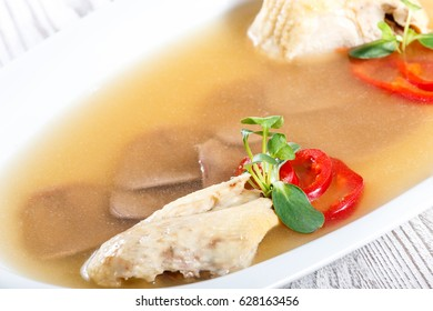 Homemade jelly chicken decorated with greens and eggs on plate on wooden background close up. Cold Meat Dishes