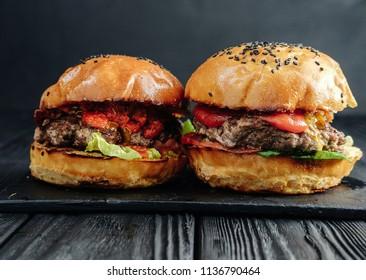 homemade juicy burgers on dark wooden board. Street food, fast food.