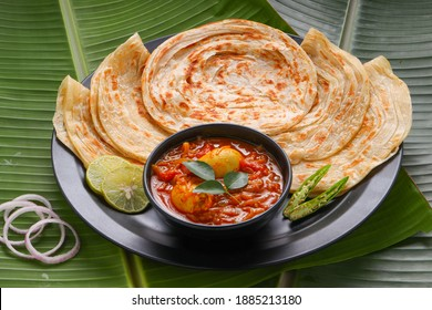 Homemade kerala Porotta or paratha,layered flat bread made using maida or all purpose wheat flour arranged in a black ceramic plate on fresh green banana leafand garnished with onion rings.