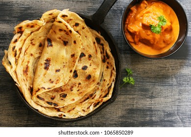 Homemade Kerala wheat paratha or layered  parotta / flat bread served with Paneer curry, top view