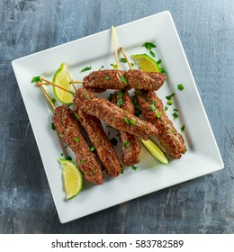 Homemade Kofta kebabs on skewers with lime and parsley on white plate