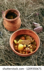 Homemade Lamb Soup Piti or Putuk with Cherry Plums in Vintage Ceramic Bowl on Rustic Background. Azerbaijani Bozbash with Mutton, Vegetables and Spices or Clear Sturdy Seasoned Broth Close Up