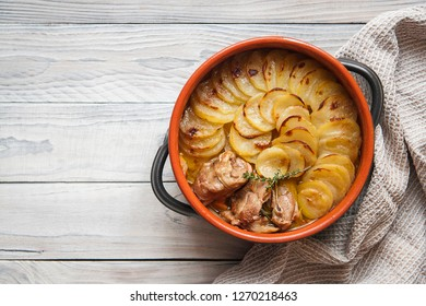 Homemade Lancashire hotpot on a light background - a stew consists of lamb, onion, carrot, Worcestershire sauce, topped with sliced potatoes, bay leaves, thyme and baked in a heavy pot on a low heat.