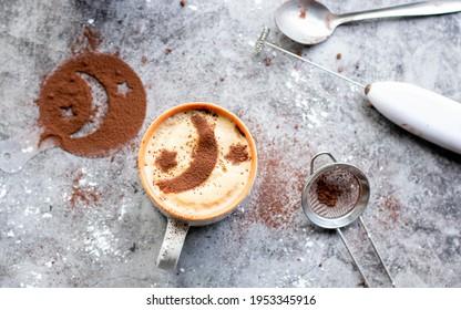 Homemade latte with moon art and utensils lying around.
