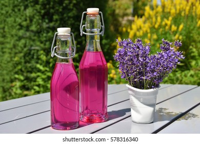 Homemade lavender syrup in glass bottles and a bouquet of lavender blossoms