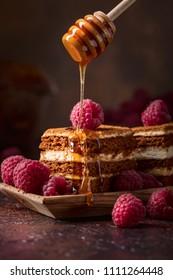 Homemade layered honey cake with cream and red raspberries.