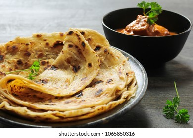 Homemade layered Paratha / Parotta or Indian flat bread served with Paneer butter masala  curry