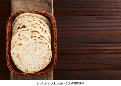 Homemade leavened Indian Naan flatbread in basket, photographed overhead on dark wood