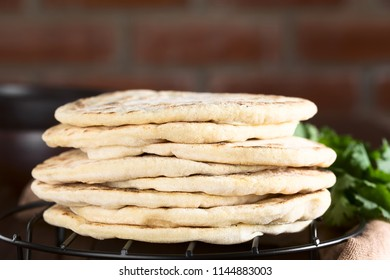 Homemade leavened Indian Naan flatbread arranged in a pile (Selective Focus, Focus on the front of the naan breads)