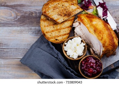 Homemade leftover thanksgiving day sandwich with turkey, cranberry sauce, feta cheese and vegetables on wooden table. Top view. Copy space