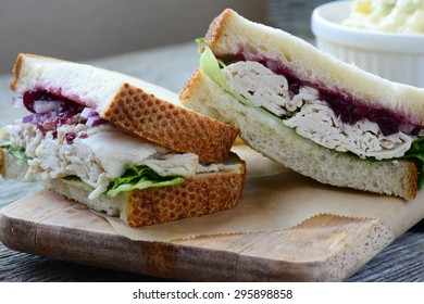 Homemade Leftover Thanksgiving Dinner Turkey Sandwich with Cranberries on Wood