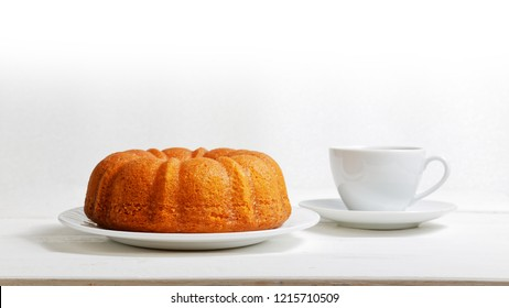 Homemade lemon cake in the form of a ring soaked with lemon syrup and cup of tea or coffee on white wooden table. Front view.
