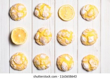 Homemade lemon crinkle cookies with powdered sugar icing. Cracked citrus biscuits on white wooden  background