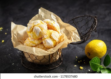 Homemade lemon crinkle cookies with powdered sugar icing on backing paper in small metal backed , on dark background