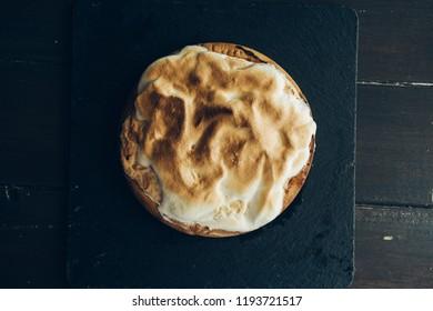 Homemade lemon meringue pie baked, with burn meringa, top view on a black board against a wooden dark table.
