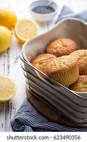 Homemade lemon poppy seed muffins on light rustic background