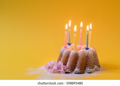 Homemade lemon ring cake with icing sugar and burning candles for birthday
