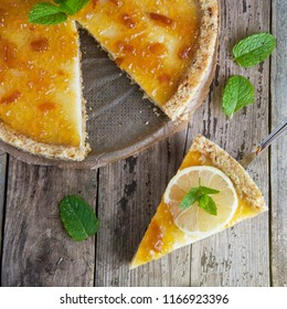 Homemade lemon tart. Sweet citrus dessert with mint leaves anc jelly cream. Rustic wooden background. Square iamge.
