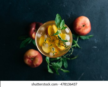 Homemade lemonade drink with fresh sweet peaches, mint leaves and thyme in glass on a dark background