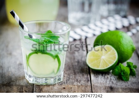 homemade lemonade with lime, mint and ice on a rustic wooden table