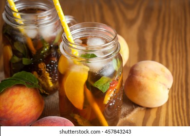 Homemade lemonade of ripe peaches and cold fresh mint. A jar of peach tea. Refreshing water.