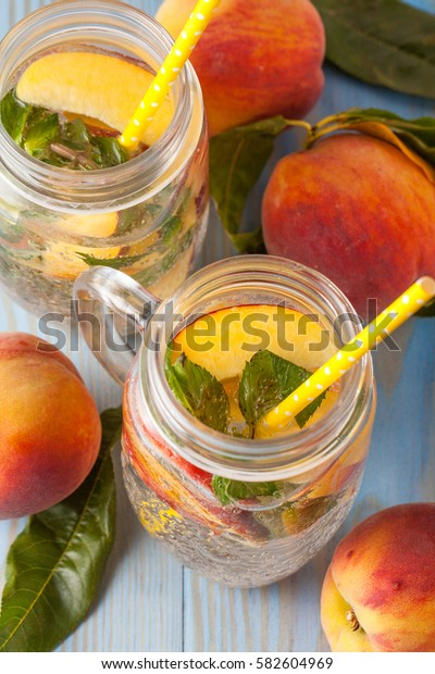 Homemade lemonade of ripe peaches and cold fresh mint. A jar of peach tea. Refreshing water.
