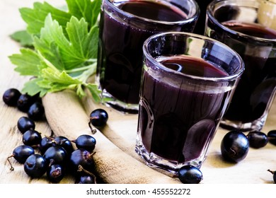 Homemade liqueur made from black currants and fresh berries, vintage wooden background, selective focus