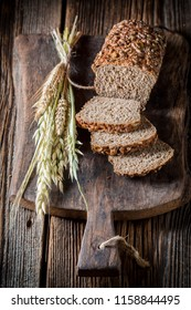 Homemade loaf of bread with grains on wooden table