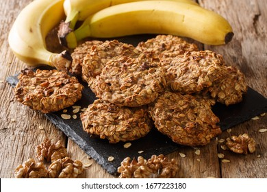 Homemade low-calorie banana cookies with oatmeal and walnuts close-up on a slate board on the table. horizontal