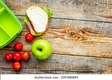 homemade lunch with apple, grape and sandwich in green lunchbox