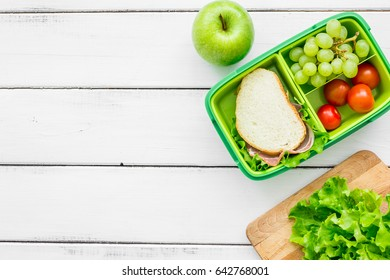 homemade lunch with apple, grape and sandwich in green lunchbox top view mockup