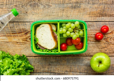homemade lunch with apple, grape and sandwich in green lunchbox top view