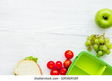 homemade lunch with apple, tomato and sandwich in green lunchbox