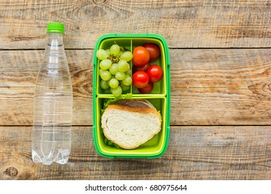 homemade lunch with bottle, grape and sandwich in green lunchbox top view mockup