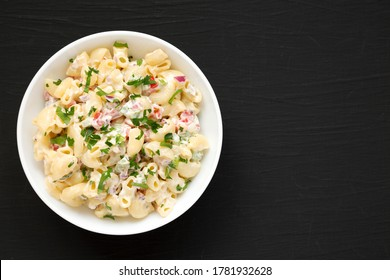 Homemade Macaroni Salad in a white bowl on a black surface, top view. Flat lay, overhead, from above. Copy space.