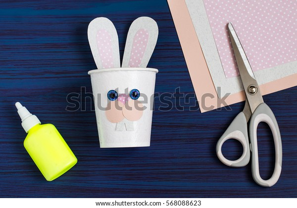 Homemade making of boxes from paper cups for sweets and candy in form of Easter hare. Present children. DIY concept. Step by step photo instructions. Step 5. Gluing nose hare