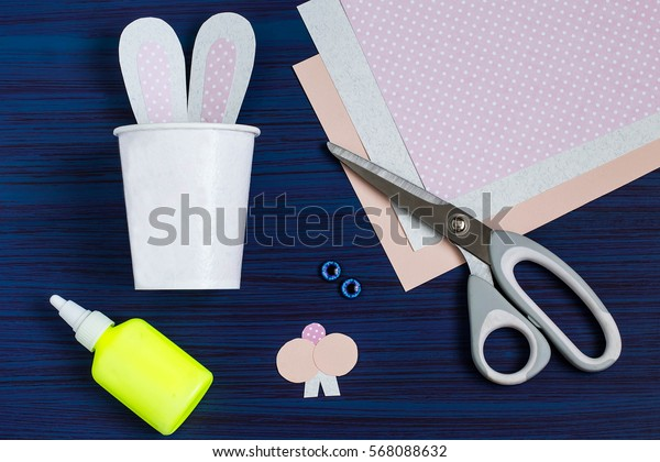 Homemade making of boxes from paper cups for sweets and candy in form of Easter hare. Present children. DIY concept. Step by step photo instructions. Step 4. Gluing rabbit ears