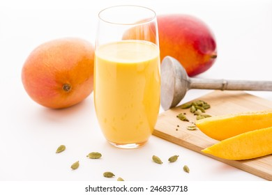 Homemade mango milkshake in a glass. Crushed cardamon seeds, mango fruit pieces and two whole mangos. Close-up. Selective focus. White background and bright kitchen table top. Studio shot.