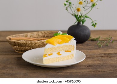 Homemade mango shortcake,sponge  soft cake on white plate decorate with ripe mango and mint on wood table. Mango is tropical fruits that make feel fresh on summer time. Sweet and sour dessert.