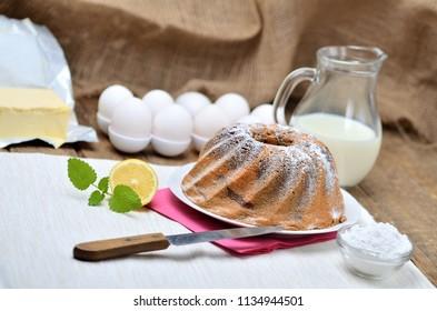 Homemade marble cake sprinkled with sugar, lemon, melissa, milk, eggs and butter