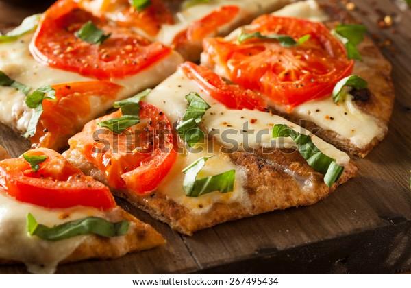 手作りのマルガリタフラットパンピザとトマトとバジル