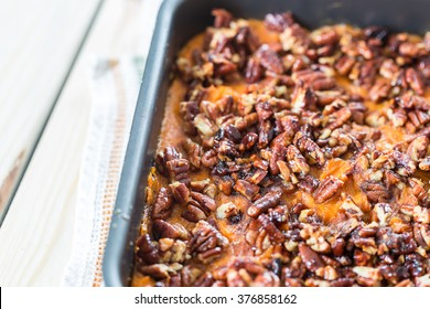 Homemade Mashed Sweet Potato Casserole with Caramelized Pecans on Light White Wooden Background, Christmas, Close-up